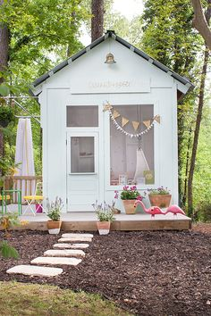 A backyard playhouse with potted flowers and mulch landscaping