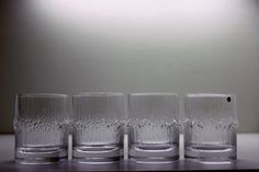 Niva- series was designed in 1972 . It was manufactured until 1992 in Iittala, Finland.  Four glasses in original factory box.  Glasses are design by Tapio Wirkkala. His inspiration came mostly from the powerful shapes of natural phenomenons. Glass series name Niva is a Finnish word for a strongly flowing river section which is characterized by a strong steady stream with only a small water undulations and vortexes on the side of the current. The last photo is for visual information. Frozen…