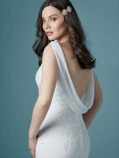 Want to look like a Roman goddess on your big day? Here's a material that looks like marble but moves like magic. A sheath low-back wedding dress with chic lines and guaranteed danceability.
