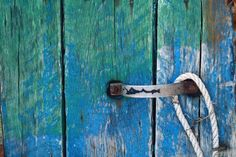 Blue and green wooden door with paint coming off.