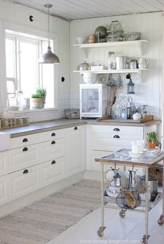 Concrete countertops and white cabinetry.