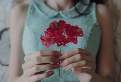 chica con flor pensando en la felicidad