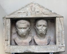 "Philonicos and Demetrius. Environs of Frascati, Italy.  P. Licinius Philonic(os) and P. Lincinius Demetrius are presumably freedmen. The left border shows the fasces; on the right is a bow and drill, a knife (or socketed chisel?), and an adze-hammer, along with a tanged chisel (without handle). The ""pediment"" on top shows a hammer, tongs, and an anvil, perhaps the set-up for a minting coins.  H: 68 cm; W; 80 cm  British Museum inv. 1954.12-14.1.  Dated by the museum to the late first…"