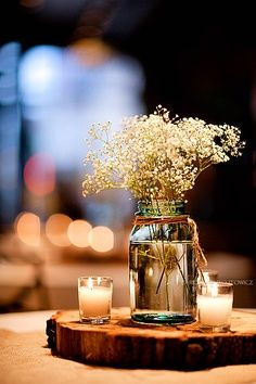 Candles surrounding flowers in a jar filled with water on top of a piece of wood