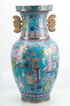 A Chinese cloisonné baluster vase, the flared mouth with upright rim decorated with a design of stylised lotus flowers and stems. The cylindrical spreading neck decorated with a vase design amongst floral and fruit motifs. The neck flanked by stylised gilt lion handles,over shoulder and sides decorated with Buddhist precious things and cherry and other blossom springing from vases of different forms. The base with Daoguang mark 1821-1850. and of period H: 45 cm.