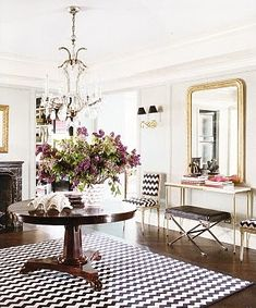 That's quite an entrance hall. Love the rug and chairs, fireplace no less!