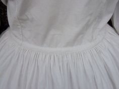 "(Maternity) Wrapper C1860 Lg Sz | eBay Interior drawstring holds it closely to the figure at back, but could be dispensed with eventually & lg amt of fabric at front would accommodate the figure. Crisp white cotton & decorated w/tiny embroidery. Self-lined in front panels, back part of skirt unlined- only faced at hem. Fastens w/tiny pearl buttons all the way to hem, can be left open from waist to show petticoat.  Note: petticoat shown NOT included.  43"" B, 31"" W. Skirt 36"" L front/39.5"" L…"