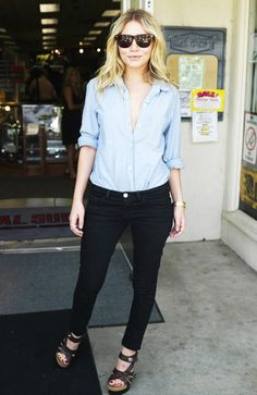 Ashley Olsen wears a boyfriend-style shirt loosely buttoned and tucked into classic black jeans.