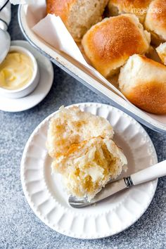 Top down view of a plate with an Instant Pot No Knead Dinner Roll that is torn in half and buttered. Above the plate a pan with more dinner rolls is visible and a small dish with butter