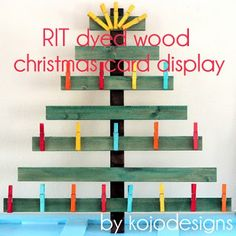 dyed wooden clothespins (and a christmas card display!) The site has ALL kinds of info on RIT Dye, links to color mixing chart, how to dye different things like wood, wicker etc. and ombre dying directions. Christmas Card Display, Christmas Tree Cards, Christmas Card Holders, Christmas Tree Decorations, Christmas Fun, Holiday Fun, Holiday Ideas, Modern Christmas, Xmas Ideas