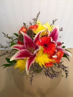 A vibrant bridal bouquet with stargazer lilies, yellow spider mums, orange gerbera daisies, and orange spray roses.