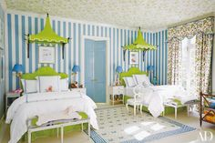 Bespoke beds by Fine Arts Furniture outfit a child's room in a Houston home designed by Miles Redd; the reproductions of Vogue covers are from the Conde Nast Collection, and the pagoda canopies are by Oscar de la Renta Home for Century Furniture. Wallpaper by Marthe Armitage animates the ceiling, while a William Yeoward for Designers Guild pattern stripes the walls.
