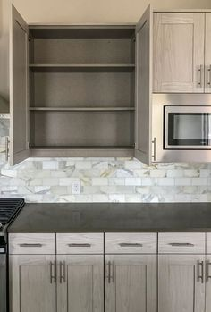 Modern gray kitchen cabinets in EVRGRN Artisk light gray with modern gray Linen cabinet interior Marble subway tile backsplash and warm, dark gray engineered quartz countertop