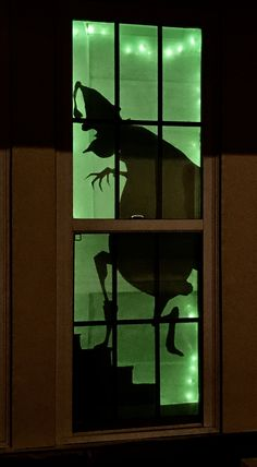 Grinch Holiday Window Silhouette. Poster board cut out with green tissue paper behind and some lights for a glow
