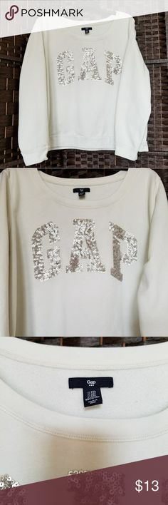 XL/XXL GAP Silver Sequin Logo Ivory Sweatshirt Spotless condition.  I don't know that it has ever been worn.  I purchased it in a pre-bundled transaction (with no measurements) and it doesn't have the length my long torso requires.  I've washed it for you so it is ready to go right out of the box.  Super soft.  Huge logo full of sequins.  Very sparkly.  Not a scoop, not a crew...I don't know what the neck is called but it's very cute! GAP Tops Sweatshirts & Hoodies