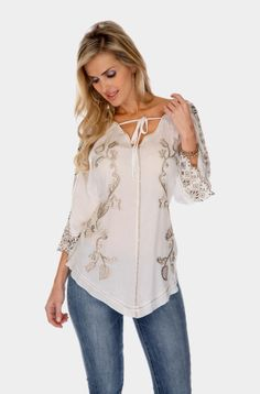 Very Elegant Tunic top with lots of detail in the front and the sleeves. The embroidery is in a soft taup color. The sleeves are wide with cutout and embroidery. The front of this tunic comes to a very unusual point. This Western Style Tunic will look great with Jeans or just about any thing Western such as one of our flowy tiered skirts. Add a Western Hat and you can go anywhere as a true Cowgirl. 100% Viscose. Hand Wash Cold. Dry Flat.This still will be available May 3...