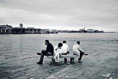 """Trieste, ore 16.59. Al tramonto, ragazzi seduti su una panchina del molo """"audace"""". Foto di Ivo Saglietti Fonte: Sette"""