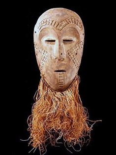 Lega Bwami Mask - Masks like these were used in instruction and initiation ceremonies into the five progressive levels of Bwami, the association that Lega men rise through with lifelong learning and deeds. Most have raffia beards. The first measurement is the height of the mask, the second is the height including the raffia.