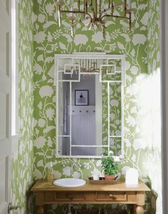 The oversize motifs of floral wallpaper and a geometric mirror punch up a tiny powder room by designer Meg Braff. Liberal dashes of white keep everything light and airy.Click through for more green decorating ideas.
