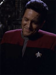"Chakotay' smile after he says, ""the way you fiddle with your combadge. You do it every time."" Janeway catches herself doing it and glares at him. He enjoys teasing her so much!"