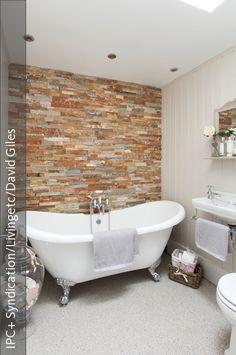 Diese freistehende Badewanne mit silberfarbene Löwenfüße steht im Kontrast zu der aufregenden Steinwand. Dieses Bad ist ein schönes Beispiel für ein kleines Badezimmer, das größengerecht eingerichtet wurde und das jede Ecke und jede Nische ausfüllt.