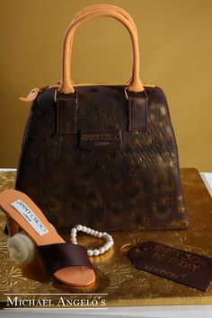 Jimmy Choo #1Handbag  This cake is covered in fondant and decorated as a replica of Jimmy Choo's brown snake skin leather top handle bag. The Jimmy Choo shoe and bracelet are hand-crafted from gum paste. A gift tag features your special birthday message.