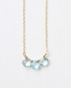 This delicate necklace features three faceted sky blue topaz briolettes suspended from a gold-filled chain. Lobster clasp closure. Can also be made in sterling silver.Blue topaz is the birthstone for December. Handcrafted birthstone jewelry by Blue Room Gems.