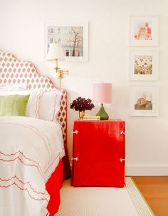 White walls, printed red headboard, white bedding with red trim, red nightstand, green and pink lamp, green and white rug, and white framed wall art