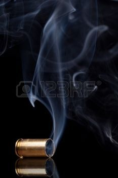 bullets: Smoking 9mm bullet casing over black background Stock Photo