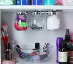 Mantén todas sus cosas pequeñas bajo control con un grupo de frascos que se adhieren magnéticamente a un anaquel del gabinete.