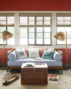 Flanked by a pair of rope-wrapped floor lamps and rattan shades, a vintage daybed covered in soft blue stripes hosts nappers and puzzle-players alike. An old trunk-turned-coffee table serves up striking weathered storage, and a round sisal rug offers a natural element underfoot.