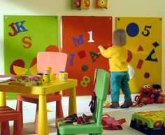 Cheery felt-covered boards hung at toddler-height sport oversized letters, numbers, and shapes.