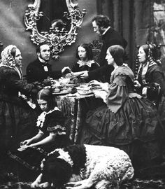 A Victorian family (including the dog) having afternoon tea.  (All those clothes!)