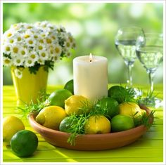 A mix of lemons and limes in a bowl, with a candle in the middles and decorated with sprengeri.