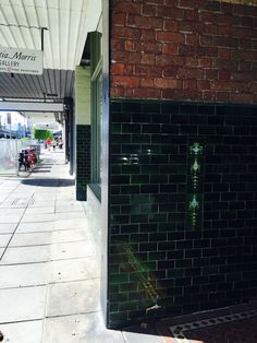 PHOTO 3: Interesting tile work, in a beautiful deep green color, contrasts beautifully with the simple red brick to create an interesting, eye catching feature wall outside this Armadale shop.