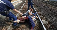 Shocking moment desperate father throws himself, his wife and baby onto rail tracks in Hungary after realising their 'train to Austria' is actually taking them to a refugee camp