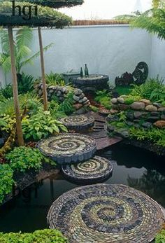 Picture Name: hampjh95 hampjh95 Patterns in circular stepping stones across water feature achieved by using different cobblestones. Oriental. Zen. Rocks. Cloud pruning pebbles paved paving steps across pond pool courtyard modern minimal contemporary wall small table and chair seat as focal point Design:Deborah Oakley RHS Hampton Court 2006 Jerry Harpur
