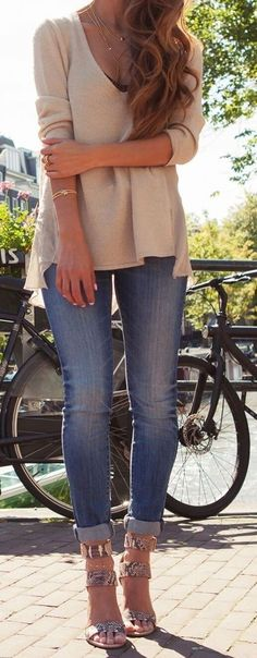25 Stylish Outfits With Cuffed Jeans: Woman in cuffed skinny jeans and beige top with a bicycle next to a lake
