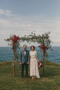 crimson peony and amaranth floral arch with olive branches