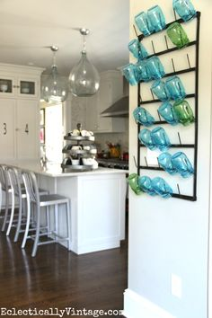 This wall bottle drying rack is huge and so cool! I love the way she used it to display colorful mason jars and she shows other creative ways to style it plus where to buy it! eclecticallyvintage.com
