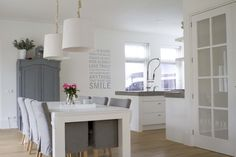 white kitchen dining room with soft grey armoire and slipcovered chairs - Jeannette uit Harderwijk - vtwonen