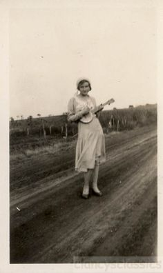 1920s cute Young Flapper era Woman Playing on BAnjo in Road