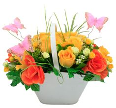 Centro de mesa con base metálica blanca. Arreglo de flores color amarillo y naranja. Manualidades