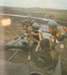 Soviet soldiers on a BMP during manouvres. One is firing an AK. ca 1980