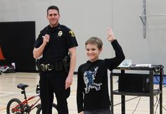 School Resource Officer Nick Schieffer shows Ian Kumsher the correct hand signals to use when biking during a lesson on bike safety. Photo by Sarina Rhinehart/Ames Tribune  http://amestrib.com/news/officials-peddle-bike-safety-mitchell