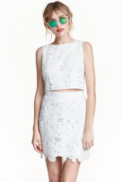Falda de encaje: Falda corta de encaje calado con pretina de grosgrain, cremallera de metal visible detrás y forro brillante.