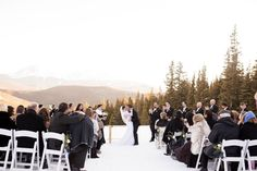 An outdoor ceremony in the snow surrounded by stunning Rocky Mountain views in Colorado.Photography by @sarahroshan