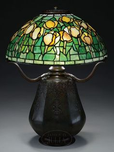 Tiffany Studios table lamp has leaded shade with pastel yellow tulips with green striated and finely mottled glass leaves. Tiffany Stained Glass, Stained Glass Lamps, Tiffany Glass, Yellow Tulips, Pastel Yellow, Studio Table, Green Highlights, Leaded Glass Windows, Lamp Light