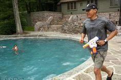 President Obama joins in a water gun fight with daughter Sasha during her 10th birthday celebration at Camp David in Maryland
