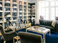 love the wall treatment....and the navy leather sofa....and the french window...and THOSE horn-backed chairs